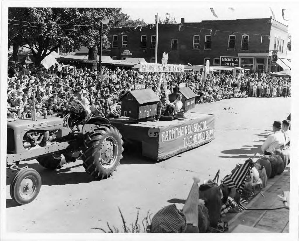 "A tractor driven by a man in glasses is pulling a parade float with two people sitting on it. On either side of the people is a small house. On the front of the float is says ""From the red school to the red barn."" There are hundreds of people lining the streets of the parade."