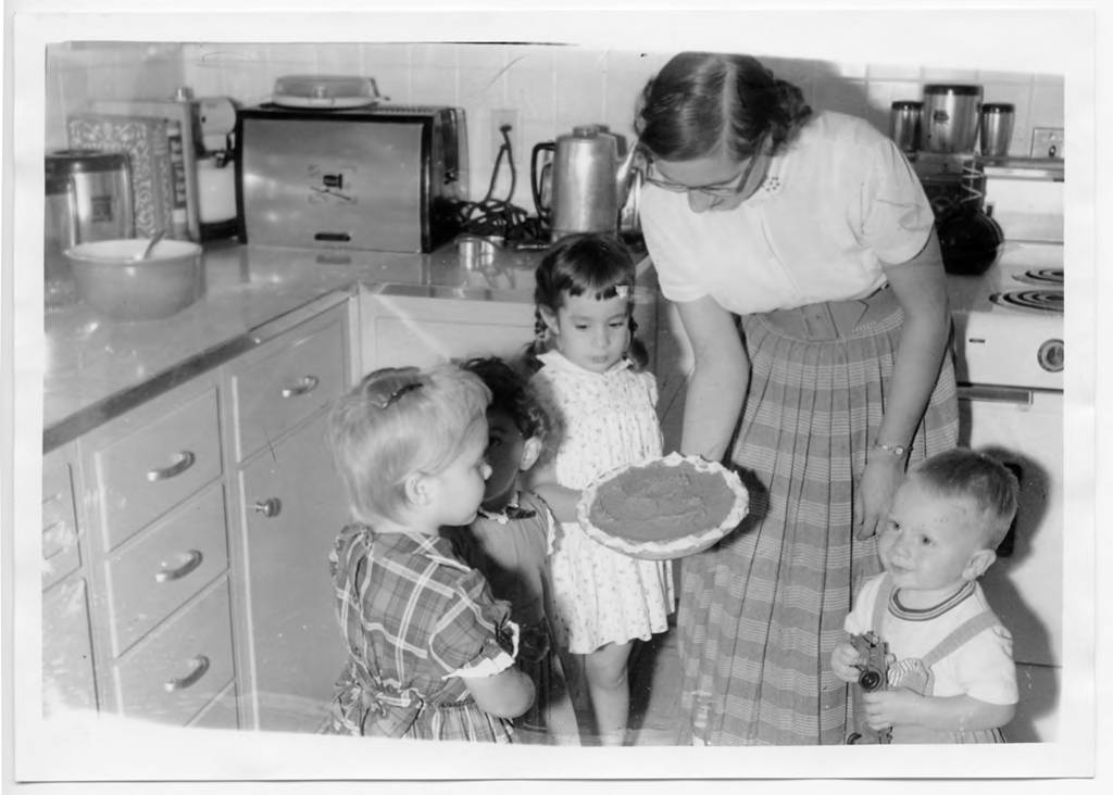 A woman and four children look at a freshly baked pie. They are standing in a kitchen.