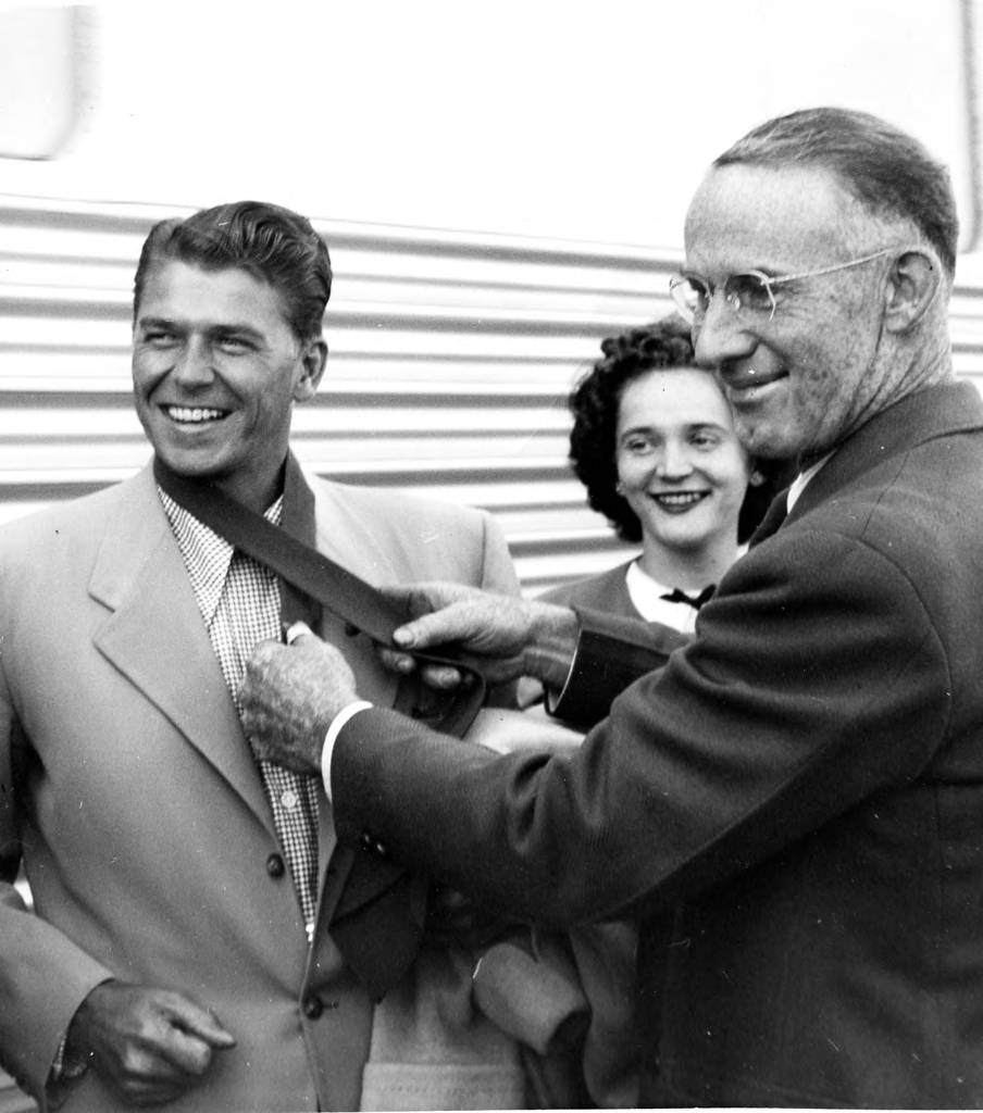 Two men and a woman are standing in front of a train. The older man, known as Mayor Bryon Britt, is tying a tie around the neck of a young Ronald Reagan. A young lady, known as Audrey Hagan, is standing in the background smiling.