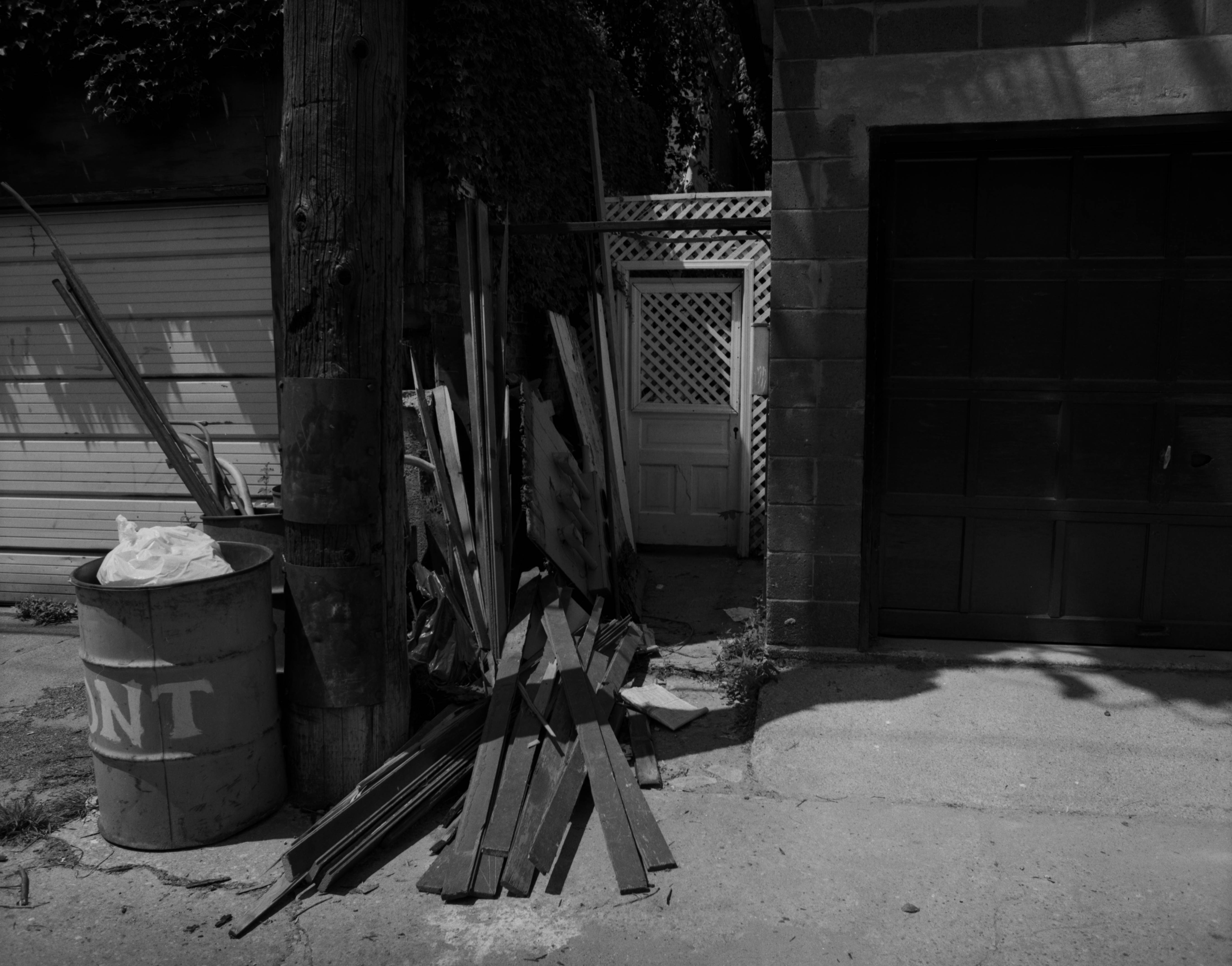 An alley with a telephone pole that is surrounded by a metal garbage bin, and pieces of wood on the ground.
