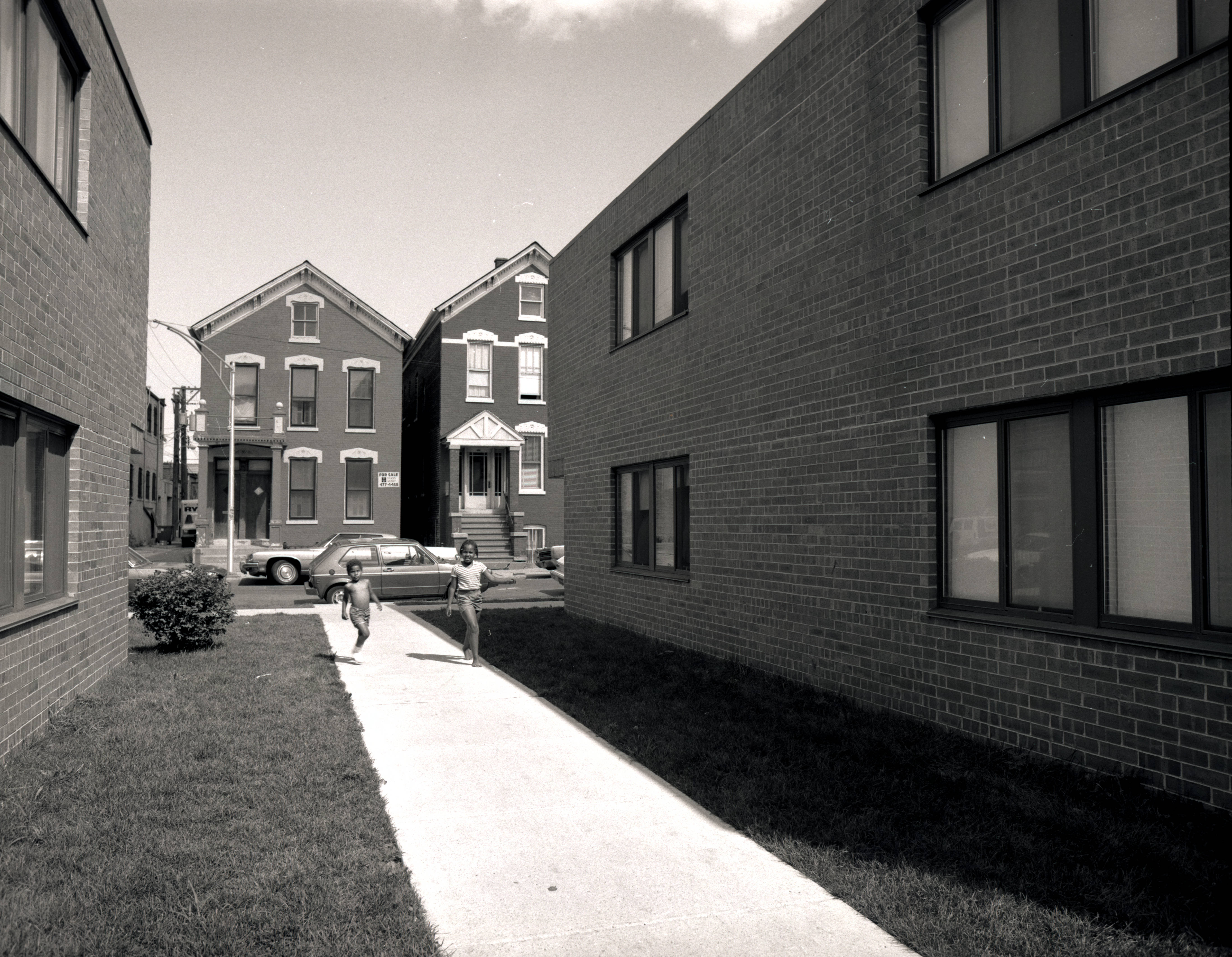 Two children are walking down the sidewalk between two new buildings.