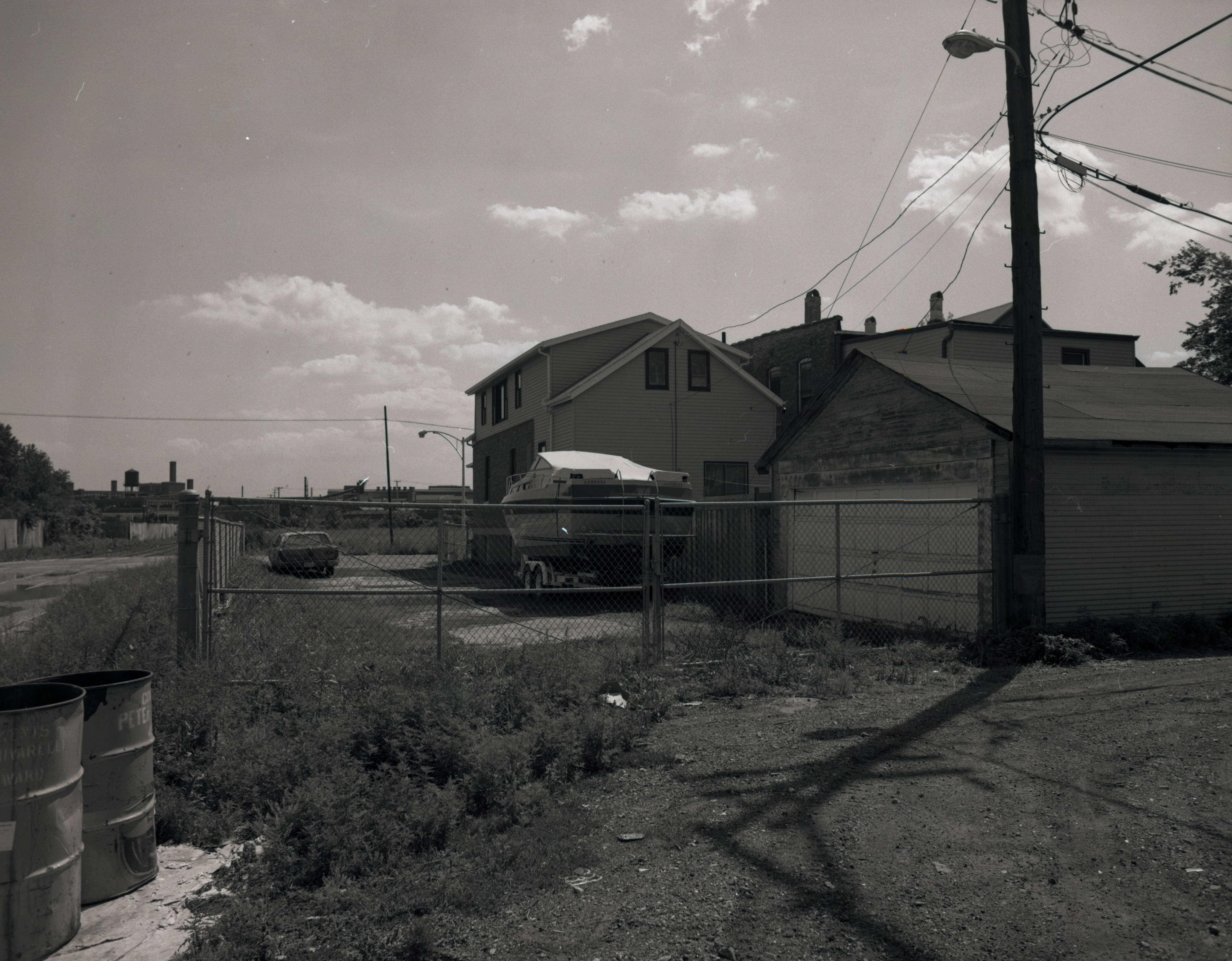 Newer homes are surrounded by chain-link fence. There is a boat on a trailer in the middle ground.