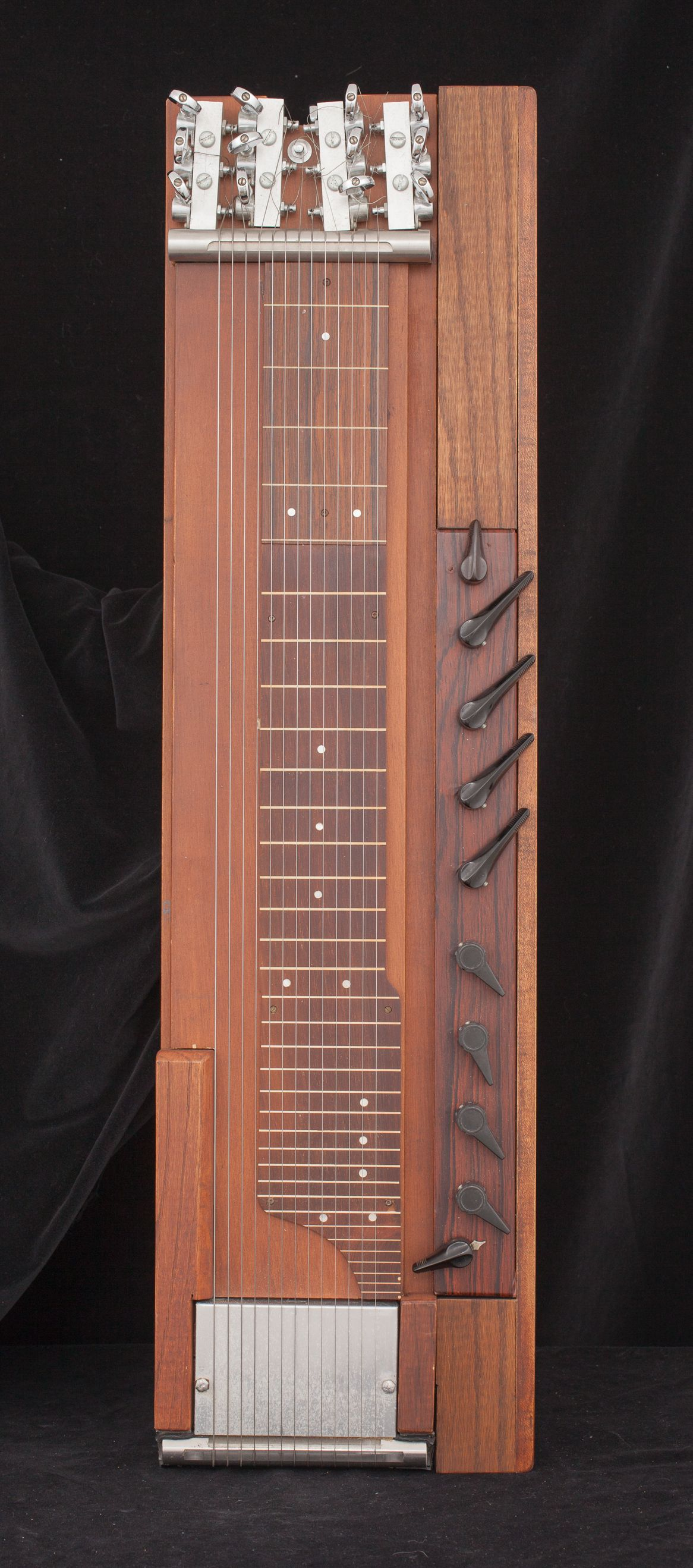 Rectangular experimental guitar made of wood. Right side has 10 levers, there are 12 strings in the center, and a metal plate at the bottom.