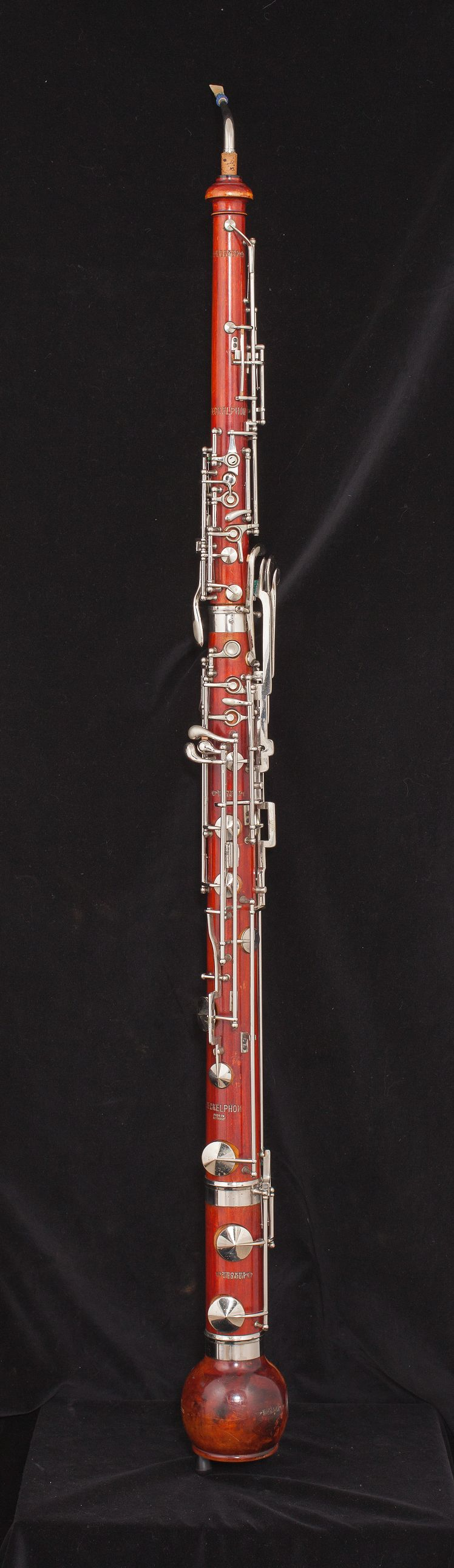 Image of a heckelphone. Double-reed instrument made of a reddish wood with metal keys.