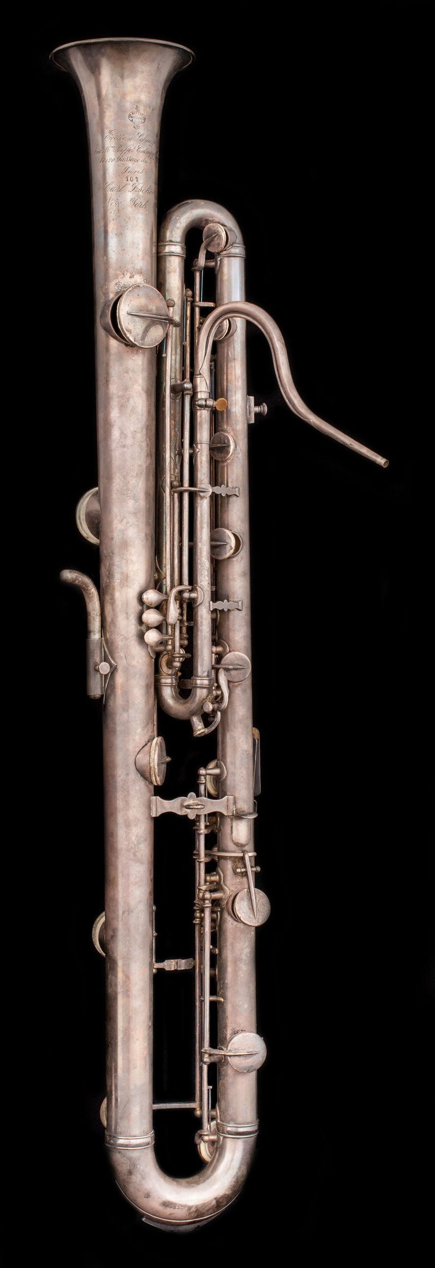 Silver instrument with keys, similar to saxophone, but with bell facing upwards.