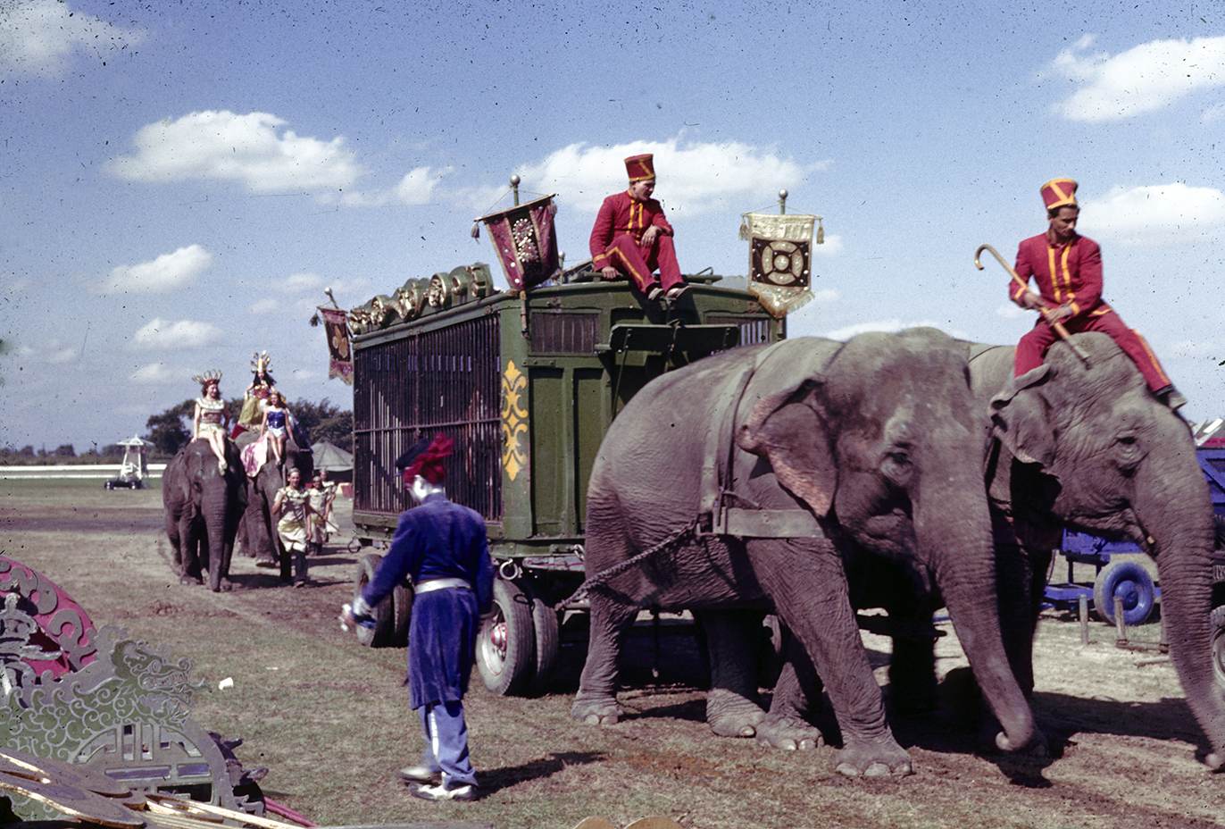 Color image of two elephants pulling green circus cage wagon. Men in red outfits sit atop one elephant and the cage wagon.