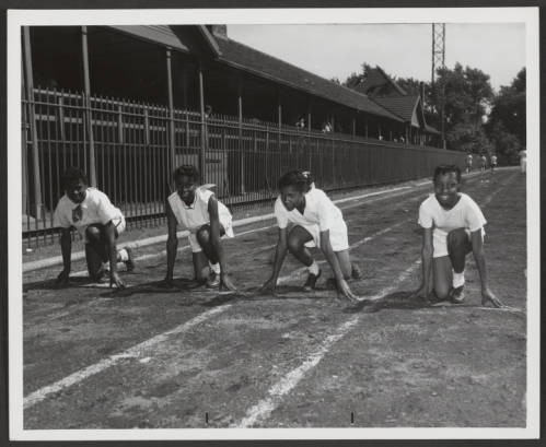 Four young women pose on a running track poised to start a sprint