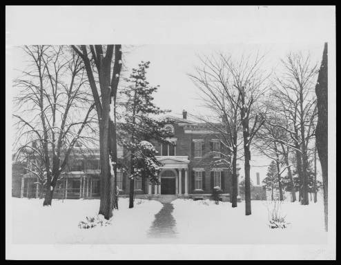 Two-story brick home with snow-covered yard in trees in the foreground