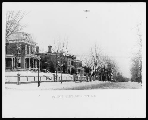 Bkack and white photograph of a snowy street next to multi-story houses