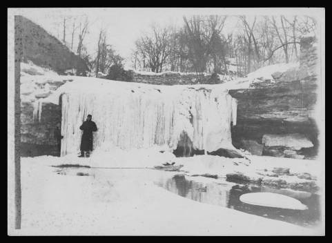 Black and white photo of a person standing in front of a frozen waterfall