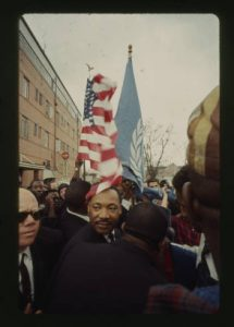 Martin Luther King, Jr. is in a crowd, an American flag flies above him