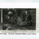 Three miners sit on a coal cart