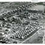 "Black and white aerial photograph of refinery tanks and stills along railroad track, with some homes in background. Top right corner labeled ""MARCH 1954"""
