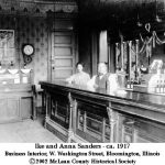 Ike and Lue Anna Brown Sanders stand behind a bar counter.