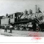Two men pose in front of a locomotive connected to a coal car and box car