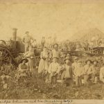 Sepia tone image depicting men and women garthered in front of a barn and farming equipment