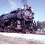 Color photo of a steam locomotive moving down the track