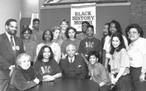 """Tuskegee Airman, Andrew Lane, sits at a table. High school students are gathered around facing camera. A banner in the background reads, """"Black History Month."""""""