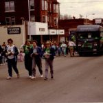Folks in green clothing walk in front of the the Quincy Public Library bookmobile during a pre-1991 St. Patrick's Day parade