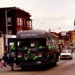 The Quincy Public Library bookmobile drives through the streets of Quincy during a pre-1991 St. Patrick's Day Parade, decked out in green balloons and ribbons