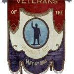 "Banner made of red velvet, white taffeta and blue velvet arranged in three descending sections. Center white section has painted blue oval featuring a statue of policeman whose right arm is raised. Gold lettering reads ""Veterans of the Haymarket Riot May 4th 1886."" Red and blue sections are bordered with gilt fringe and tassels. Hung from a tin rod with six pointed stars on either end."