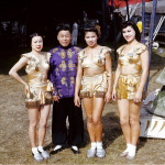 Family of performers line up for a camera. (left to right) Nio Naitto, her father Ala Naitto, and Margie Naitto. Ala is dressed in a purple and gold long-sleeve shirt. His daughters are dressed in matching gold tops and bottoms.