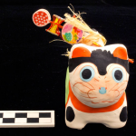 One piece molded and painted cat figure. Painted red, white and green. Has wooden toy and silk rattle on back