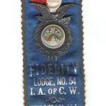 Beautiful silk ribbon with badge, from a member of the Fidelity Lodge No. 54 of the International Association of Car Workers. Front side is Blue silk with silver lettering, back side is black silk with silver lettering and designs and says Newark, New Jersey at the top and IN MEMORIAM.
