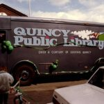 Quincy Public Library BookMobile decked out in St. Patrick's Day-themed green balloons and ribbons. Text on the side of the bookmobile reads Quincy Public Library:Over a Century of Serving Quincy