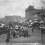 View of the Randolph Street Haymarket Square in 1886. Horse-drawn carriages line a narrow dirt street between rows of brick buildings