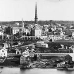 1871 East Elgin Panorama Looking at east Elgin along the Fox Riverbank. The Congregational Church is in the center of the photograph with the First Universalist Church to the left with four short steeples. Behind the Universalist Church is the Old Stone Baptist Church a small steeple.