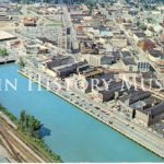 Aerial color photo of downtown Elgin. The Fox River runs through the city, next to riverfront development.
