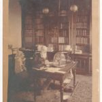 Sepia tone photograph of the Illinois State Museum's first curator, Amos Henry Worthen. Worthen, with a white long beard, sits behind a desk covered in books, paperwork, and instruments, a massive book case looming in the background
