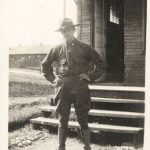 Sepia-tone photograph of a soldier standing in front of a building