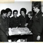 Six women in army uniforms gather around a map. Two point to a location in Southeast Asia