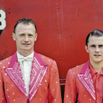 Man and son, standing side-by-side, dressed in bright pink and orange suits with rhinestones look into the camera