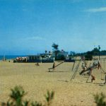 Postcard picturing children playing on a swingset on a beach