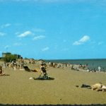 Postcard picturing sunbathers lying on a beach while people in the background wade in the shallows