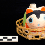 One piece molded and painted papier mache cat in basket. Painted red, white and green