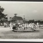 Black and white photo of a playground with children on a merry-go-round