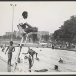 Black and white photo of people at a pool. A lifeguard sits on a platform in the foreground.