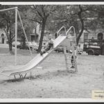 Black and white photo of two children playing on a playground slide