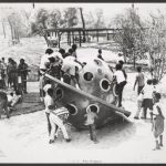 Black and white photo of several children playing on a piece of playground equipment shaped like a ringed planet