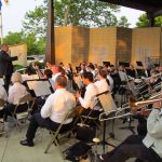 An orchestral band including brass instruments, woodwinds, and percussion, performs outside in a band shell