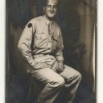 Black and white photograph of a man in a World War II-era army uniform, seated
