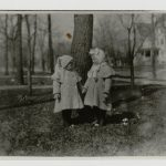 Black and white photo of Marcelline and Ernest Hemingway as very young children dressed in winter attire and holding hands in front of a large tree.