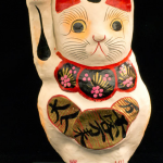 Cat figure, painted white and red. Called 'Maneki-Neko' in Japanese. Used to set in store window to invite customers in and bring good luck